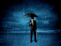 Business man standing in rain with an umbrella Royalty Free Stock Image