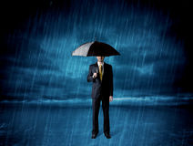 Business man standing in rain with an umbrella Royalty Free Stock Photography