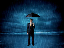 Business man standing in rain with an umbrella Stock Photos