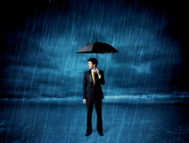 Business man standing in rain with an umbrella Royalty Free Stock Photos