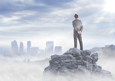 Business man standing on rock looking at misty skyline Stock Photos