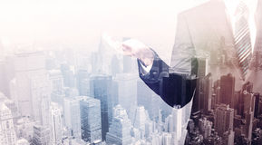 Business man standing on roof with city in the background Royalty Free Stock Image