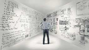 Math formulas on walls. Business man standing in a room and studying math formulas written on walls Stock Photos