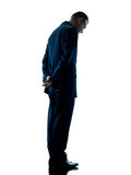 Business man standing sadness silhouette isolated. One caucasian business man standing sadness silhouette isolated on white background Stock Photo