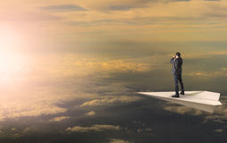 Business man standing and spying binocular on papet plane agains Stock Images