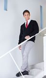 Business man standing on stairs. Happy attractive business man standing on stairs in the office Stock Photo
