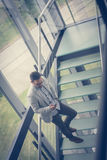 Business man standing on the stairs of business building. Royalty Free Stock Images