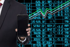 Business man standing with stock market Stock Photos