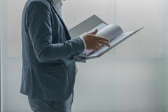 Business man standing and reviewing a document in file. Business man standing to review a document in file at office stock photos