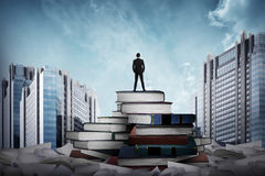 Business man standing on the top of books Royalty Free Stock Photos