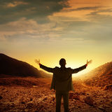 Business man standing top of the mountain. When sunset come Royalty Free Stock Images