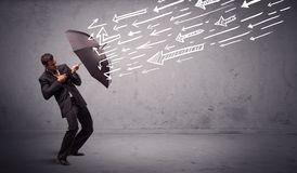 Business man standing with umbrella and drawn arrows hitting him Royalty Free Stock Photos