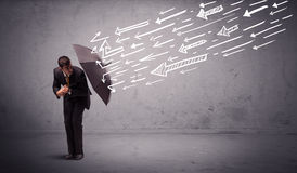 Business man standing with umbrella and drawn arrows hitting him Stock Photo