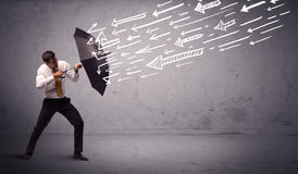 Business man standing with umbrella and drawn arrows hitting him Stock Images