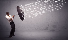 Business man standing with umbrella and drawn arrows hitting him Stock Photography