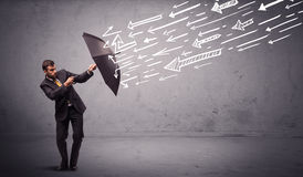 Business man standing with umbrella and drawn arrows hitting him Royalty Free Stock Photo