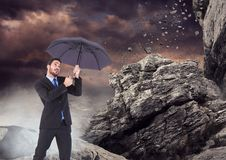 Business man standing with umbrella and mist against falling rocks. Digital composite of Business man standing with umbrella and mist against falling rocks Royalty Free Stock Photo