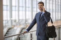 Business man standing walking talking on his cell phone Royalty Free Stock Image