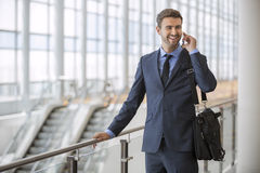 Business man standing walking talking on his cell phone Stock Photography