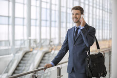 Business man standing walking talking on his cell phone stock photo