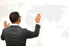 Business man standing with world map on white wall. Business man standing with a world map on white wall Stock Images