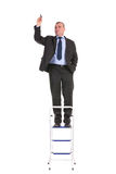 Business man stands on ladder and draws Stock Photo