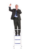 Business man stands on ladder and writes Royalty Free Stock Image