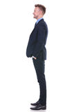 Business man stands sideways and smiles Royalty Free Stock Photography