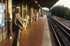 A business man stands waiting for a Metro rail commuter train at sunrise, National Airport, Washington, D.C. Royalty Free Stock Photography