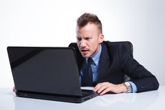 Business man stares at his laptop. Young business man saring at his laptop. on a gray studio background Royalty Free Stock Photos