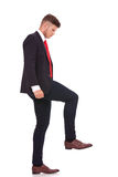Business man stepping on something Royalty Free Stock Photography