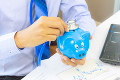 Business man with stethoscope checking piggy bank , financial di Royalty Free Stock Photo