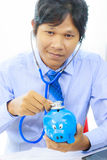 Business man with stethoscope checking piggy bank , financial di Stock Photo