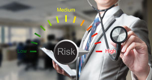 Business man with stethoscope examining risk Stock Images
