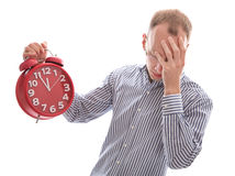 Business man stressed with a alarm clock in red. Eleventh hour - stressed man holding clock hiding behind hand isolated on white background royalty free stock photo