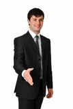 BUSINESS MAN STRETCHING HIS HAND FOR A HANDSHAKE. Portrait of positive business man stretching his hand for a handshake Royalty Free Stock Image