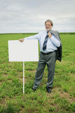Business man on strick. Senior business man with jacket on shoulder and blank board in a meadow Royalty Free Stock Photography