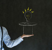 Man pulling idea from magic hat blackboard background. Business man, student or teacher pulling idea from a magic hat on blackboard background Stock Images