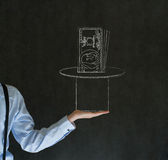 Man pulling money from magic hat blackboard background. Business man, student or teacher pulling money from a magic hat on blackboard background Stock Photo