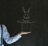 Man pulling rabbit from magic hat blackboard background Royalty Free Stock Photo