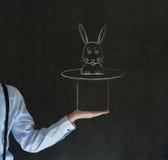 Man pulling rabbit from magic hat blackboard background Royalty Free Stock Photo