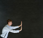 Man pushing on blackboard background Stock Photos