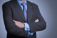 Business man in a stylish suit standing with folded arms.  royalty free stock photography