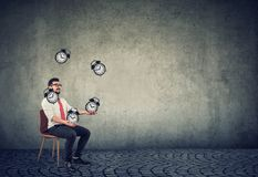 Business man successfully juggling managing his time. Happy business man successfully juggling alarm clocks managing his time royalty free stock photography