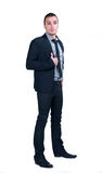 Business man in suit. Full length studio portrait of young confident successful office worker wearing modern stylish black suit, stripped shirt, tie, holding the Royalty Free Stock Photo