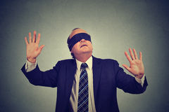 Business man in suit blindfolded stretching his arms out Stock Photos