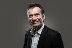 Business Man in Suit with Cheesy Grin High Contras. Handsome Middle Age Business Man in Suit with Cheesy Silly Grin on Grey Background High Contrast Grunge Look Stock Photos