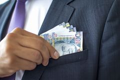 Business man in a suit concealing 100 soles bills, Peruvian currency concept royalty free stock photos