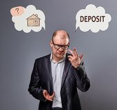 Business man in suit and eyeglasses looking and thinking - deposit or buying the house. Concept illustration with house in bubble. Cloud and deposit word stock photo