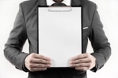 Business man in suit holding a blank clipboard. Isolated on white Stock Image